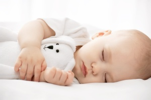 Carefree sleep little baby with a soft toy on the bed