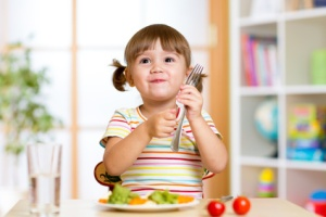 child girl eats healthy food vegetables at home or kindergarten