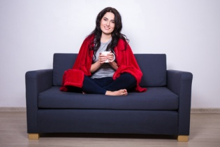 young woman sitting on sofa with mug of tea wrapped in red blank